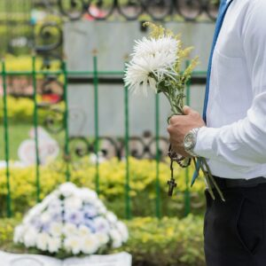 Person taking flowers to a loved one's grave